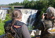 2 motorcycle riders taking a photograph of a waterfall