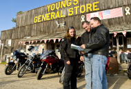 3 motorcycle riders with motorcycles looking at map in front of young's general store