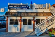 a building with stairs leading to roof with blue sign that ready the Bayfield Inn