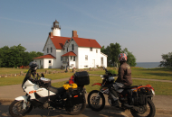 2 motorcycles parked in front of a lighthouse with water in the distance